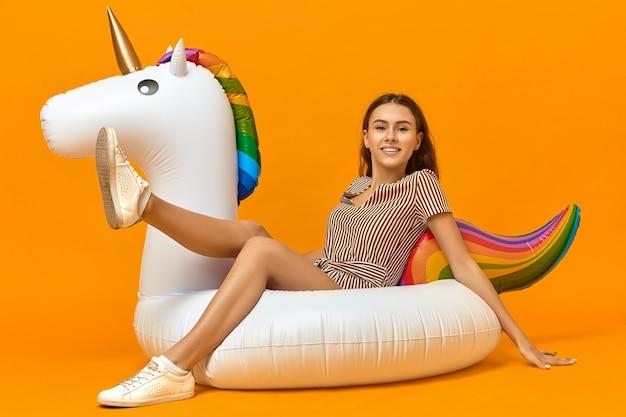 Imagem horizontal de uma jovem caucasiana feliz e radiante com tênis branco e vestido listrado