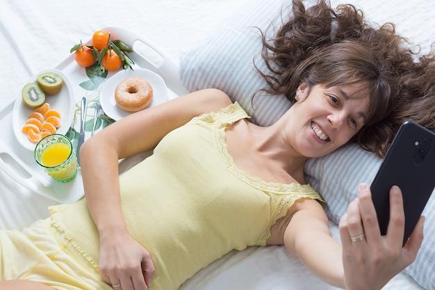 Imagem horizontal de uma jovem sorridente de cabelos castanhos deitada na cama com uma camiseta amarela tirando uma selfie ao lado de uma bandeja de café da manhã na luz suave da manhã Foto Premium