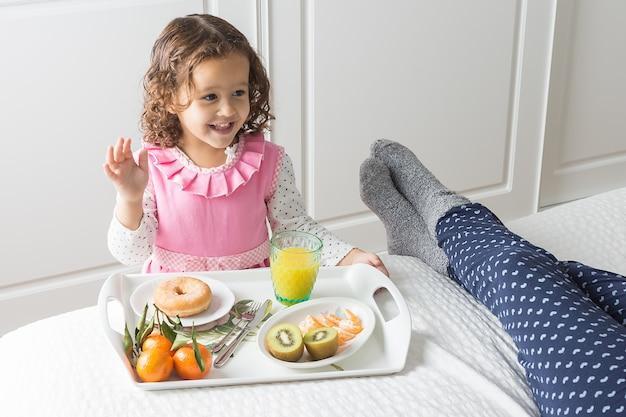 Imagem horizontal de uma menina sorridente em um vestido rosa e branco carregando uma bandeja com um café da manhã para a cama com sua mãe de pijama com luz lateral suave
