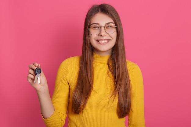 Imagem interior da adorável jovem fêmea magnífica segurando as chaves, sorrindo sinceramente,