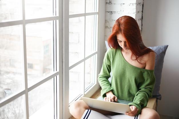 Imagem interna de estudante sério fazendo lição de casa no laptop. adolescente elegante com cabelo ruivo liso sentado no parapeito da janela, usando um computador portátil, assistindo a um videoblog ou fazendo compras online