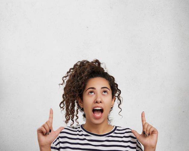 Imagem interna de uma mulher encaracolada chocada e excitada aponta para cima com os dedos ao ver algo estranho,