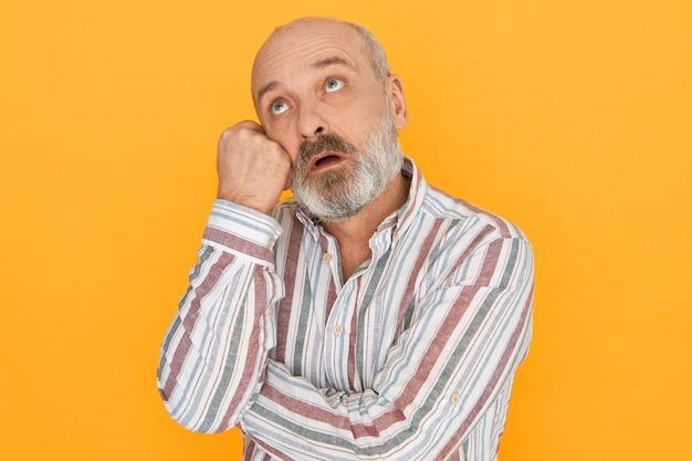 Imagem isolada de bonito pensativo barbudo caucasiano pensionista do sexo masculino com expressão confusa e intrigada, tendo problemas de memória, segurando a mão no rosto e olhando para cima, tentando se lembrar de algo.