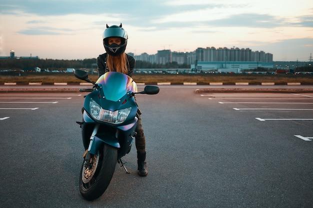 Imagem isolada de comprimento total de uma jovem mulher elegante e ativa com cabelo loiro, usando um capacete de segurança, posando contra edifícios de vários andares, sentada em uma motocicleta com um pé na calçada