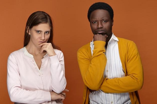 Imagem isolada de equipe inter-racial de dois colegas trabalhando juntos, tentando se lembrar de algo em mente, de mãos dadas no rosto, com olhares pensativos, preocupados com algum problema