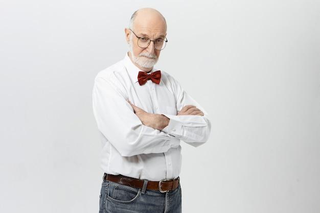 Imagem isolada de homem sério aposentado confiante, com cabelo careca e barba por fazer, posando em postura fechada com os braços cruzados, expressando suspeita e dúvida, olhando, usando óculos