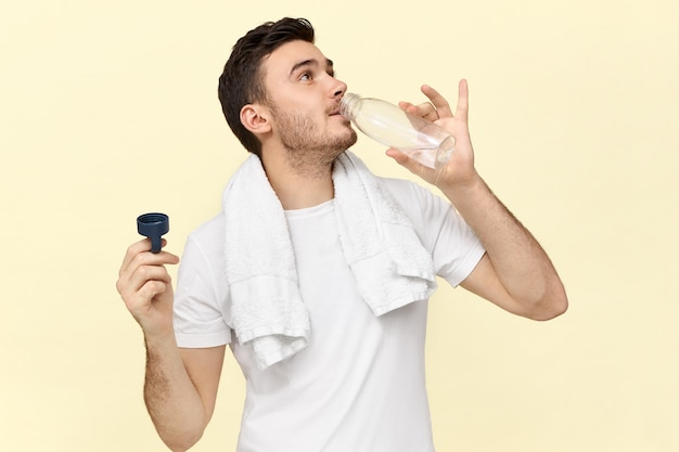 Imagem isolada de jovem bonito e confiante com uma toalha em volta do pescoço, segurando uma garrafa de plástico, se refrescando após o exercício físico na academia, bebendo água avidamente, vestindo uma camiseta branca