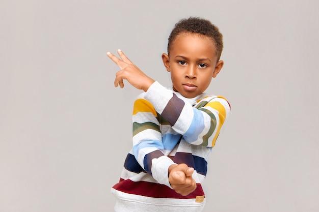 Imagem isolada de um garoto afro-americano bonito e confiante usando um macacão listrado, apontando para uma parede em branco, mostrando dois sinais com os dedos e olhando para a direita com olhar sério
