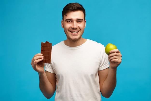 Imagem isolada de um jovem emocional bonito, mantendo uma dieta rigorosa sem açúcar, segurando uma maçã verde e uma barra de chocolate ao leite, com uma expressão animada, indo comer comida proibida como refeição enganadora