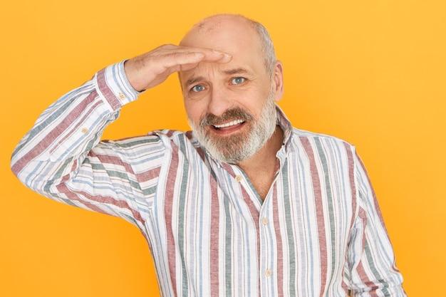 Imagem isolada de um lindo avô barbudo europeu com problemas de visão, segurando a mão na testa, concentrando a expressão facial, procurando por algo ao longe
