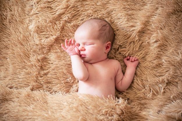 Imagem lacônica de um bebezinho colocado em uma superfície fofa fechando os olhos escondidos e tocando o rosto