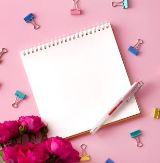Imagem lisa colocada com o bloco de notas aberto vazio e os acessórios diferentes na superfície colorida.