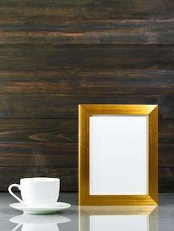 Imagem mock up com moldura dourada e xícara de café sobre a mesa com fundo de parede de madeira