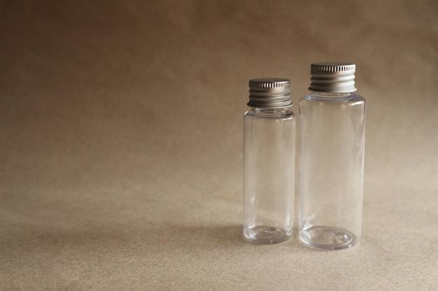 Imagem modelo de uma garrafa de vidro transparente com uma tampa de metal em um fundo marrom