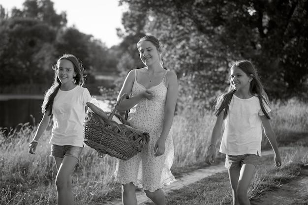 Imagem monocromática de mãe feliz com filhas caminhando em um prado