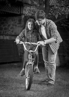 Imagem monocromática de pai feliz ensinando a filha a andar de bicicleta
