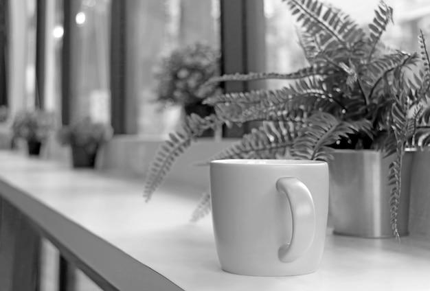 Imagem monótona de uma caneca de café com samambaias em vasos borradas em uma mesa comprida