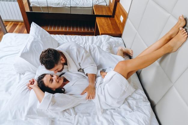 Imagem mostrando casal feliz descansando no quarto de hotel