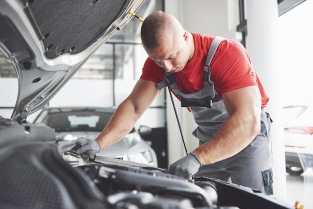 Imagem mostrando o trabalhador de serviço de carro musculoso reparando o veículo.
