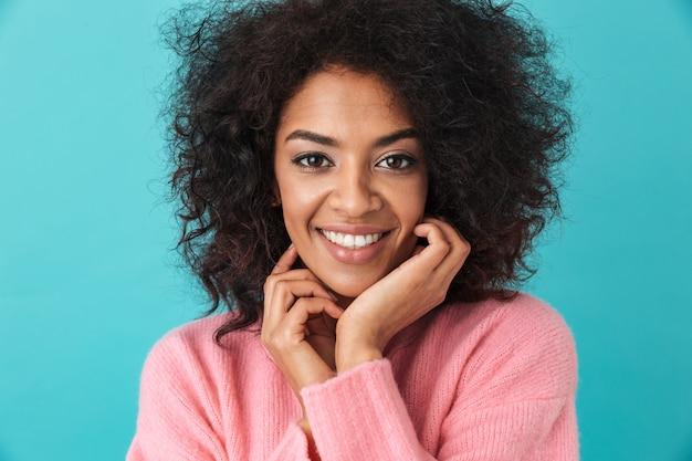 Imagem multicolorida de uma linda mulher de 20 anos com penteado afro, sorrindo com os dentes brancos perfeitos, isolados sobre a parede azul