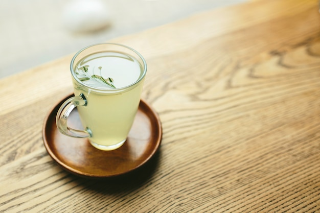 Imagem ou copo de vidro com chá verde ou branco. fique no prato. não existem pessoas. luz do dia. fechar-se.