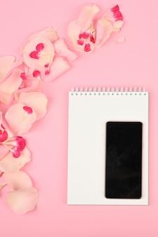 Imagem para o blog das mulheres. postura plana com flores, caderno, smartphone e lápis no espaço de papel