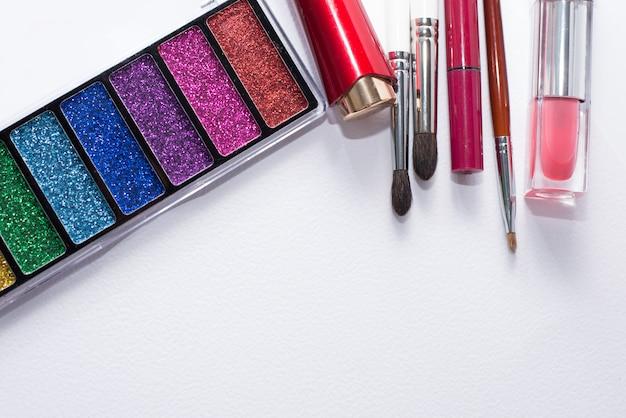 Imagem plana leigos de cosméticos beleza compõem com batons, paleta de sombra, pincéis, brilho labial. fundo branco