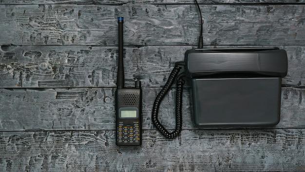 Imagem preto e branco de um walkie-talkie e telefone em uma mesa de madeira.