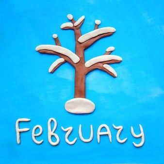 Imagem quadrada com árvore de plasticina na neve branca e a palavra fevereiro