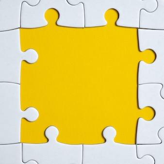 Imagem quadrada de um quebra-cabeça branco sobre um fundo amarelo. fechar-se. postura plana.