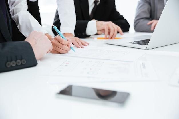 Imagem recortada da equipe de negócios perto da mesa com laptop e documentos