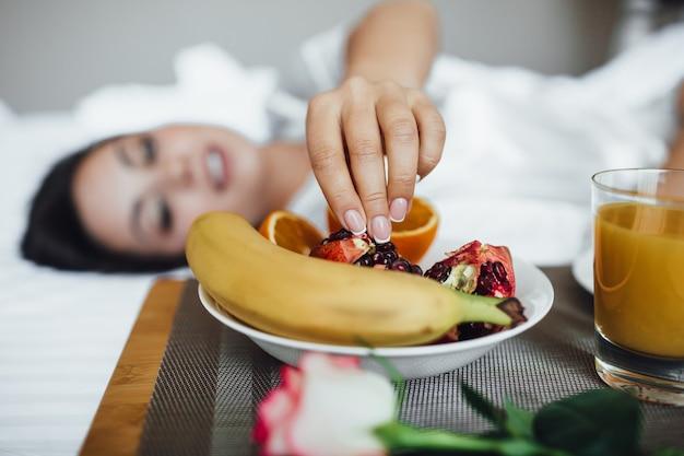 Imagem recortada da linda menina morena pela manhã, ao lado de croissant, suco de laranja e romã de banana na bandeja e rosa