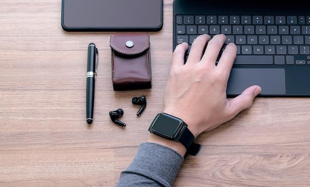 Imagem recortada da mão do homem usando smartwatch, trabalhando no teclado do tablet, vista superior, copie o espaço.