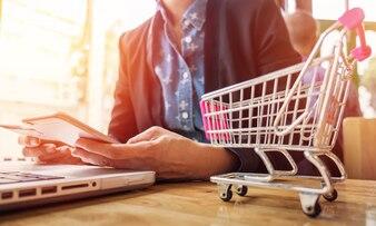 Imagem recortada da mulher que fornece informações sobre cartões e chave no telefone ou laptop enquanto faz compras on-line.