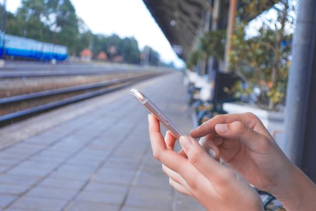 Imagem recortada das mãos da mulher segurando o telefone móvel com tela de espaço em branco da cópia