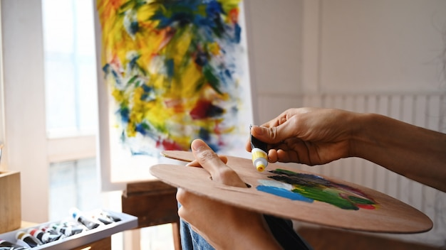 Imagem recortada das mãos do artista mulher bonita enquanto mistura a cor na paleta de cores de madeira