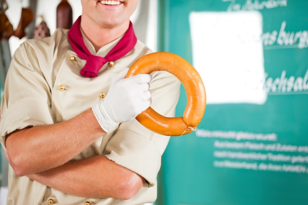 Imagem recortada de açougueiro sorrindo enquanto segurando salsicha