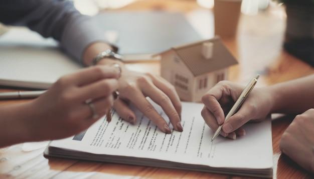 Imagem recortada de agente imobiliário auxiliando o cliente a assinar o papel do contrato na mesa com a maquete da casa
