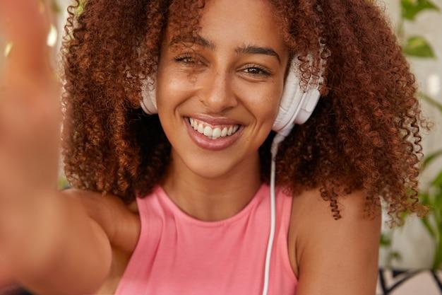 Imagem recortada de alegre mulher negra mestiça com cabelo crespo, faz selfie retrato, ouve faixa de áudio em fones de ouvido, está em alto astral, tem tempo livre depois de aulas, desfruta de um emocionante livro de áudio