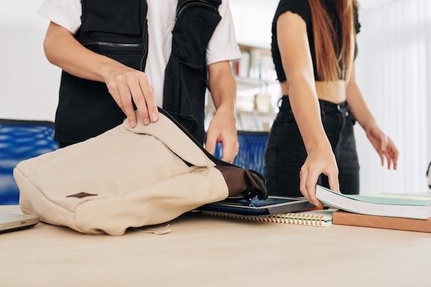 Imagem recortada de alunos adolescentes colocando livros e tablets em bolsas após o término das aulas