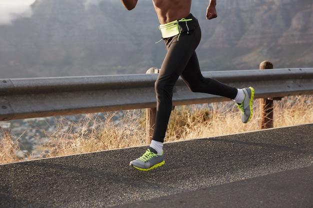Imagem recortada de atleta corredor correndo em estrada, fotografado em movimento, usa tênis confortável, participa de marafone. concentre-se a pé. esportista leva estilo de vida saudável, cobre o destino