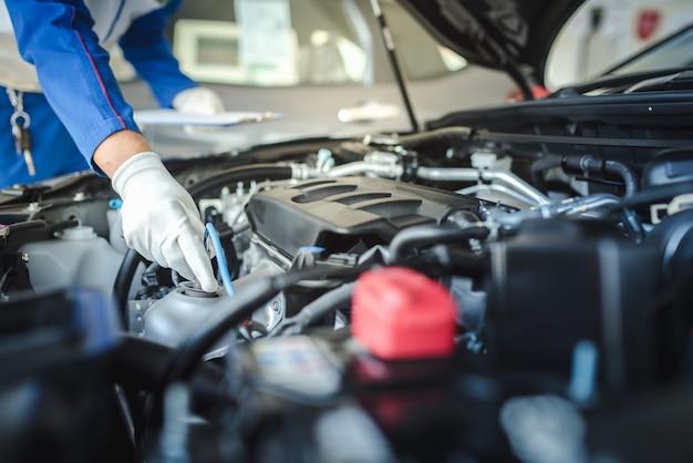 Imagem recortada de bonito mecânico de uniforme está trabalhando no serviço de auto. reparação e manutenção de automóveis.