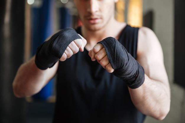Imagem recortada de boxeador em pé no ginásio