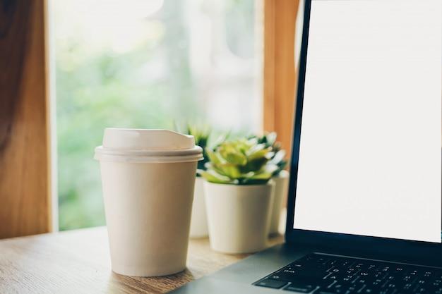 Imagem recortada de café e laptop na mesa de madeira