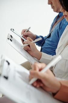 Imagem recortada de candidatos a emprego preenchendo dados em formulários de cv ao aguardar a entrevista com o gerente de recursos humanos