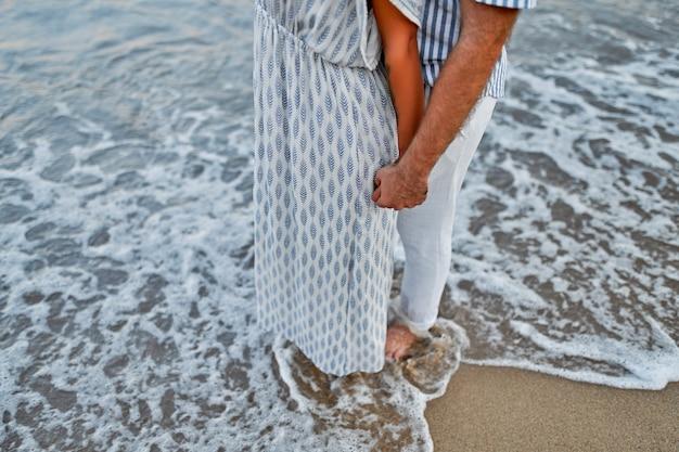 Imagem recortada de close-up de um jovem casal amoroso à beira-mar, de mãos dadas, curtindo um ao outro e as férias, romanticamente passando tempo na praia.