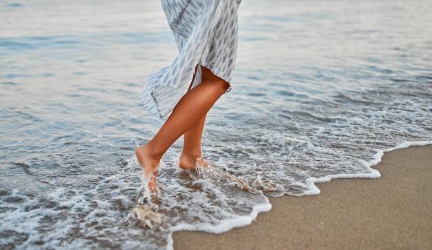 Imagem recortada de close-up de uma mulher com um vestido caminhando à beira-mar na água.