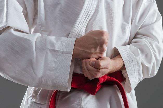 Imagem recortada de desportista vestido de quimono, pratica caratê e gesto com mão isolada sobre fundo cinza.