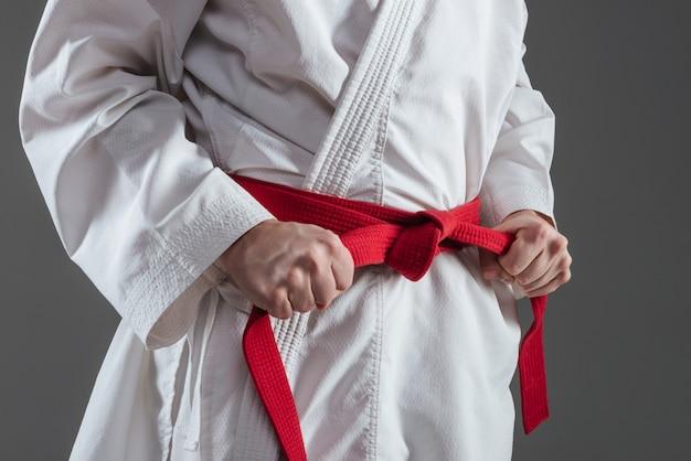 Imagem recortada de desportista vestido de quimono praticando caratê enquanto aperta o cinto vermelho isolado sobre fundo cinza.