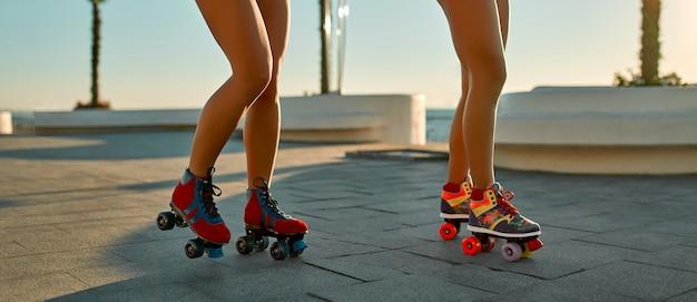 Imagem recortada de duas mulheres em patins em trajes de banho perto da praia em um dia ensolarado.